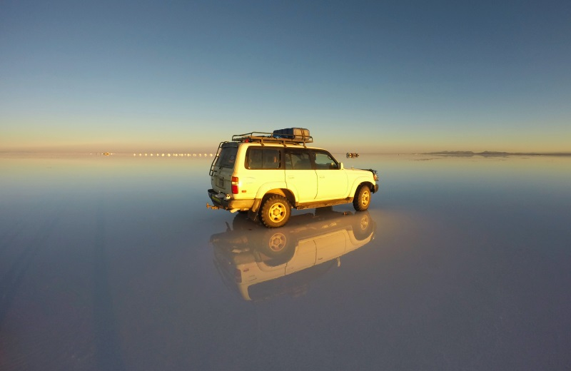 Jeep no Salar de Uyuni alagado durante o nascer do sol, Bolívia